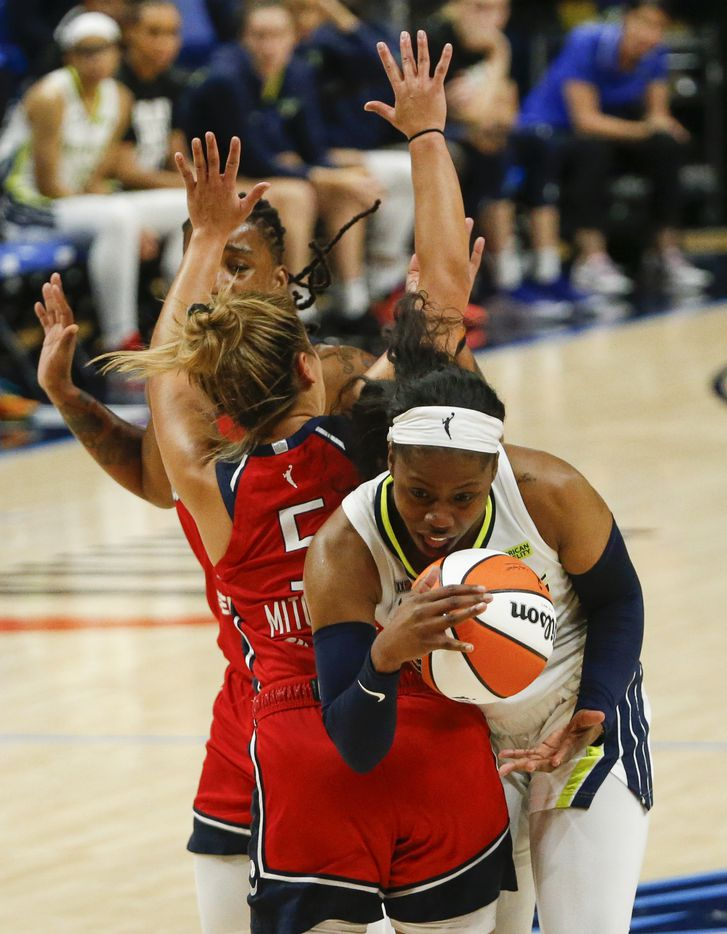 Dallas Wings guard Arike Ogunbowale (24) collides in the paint with Washington Mystics guard Leilani Mitchell (5) during the third quarter at College Park Center on Saturday, June 26, 2021, in Arlington. (Elias Valverde II/The Dallas Morning News)