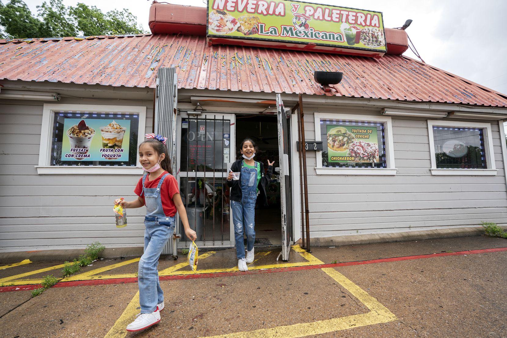 Isabella Melendez (left), 6, and her sister Sophia Melendez, 9, leave La Mexicana Neveria y Paleteria across from Winnetka Elementary School on Thursday.