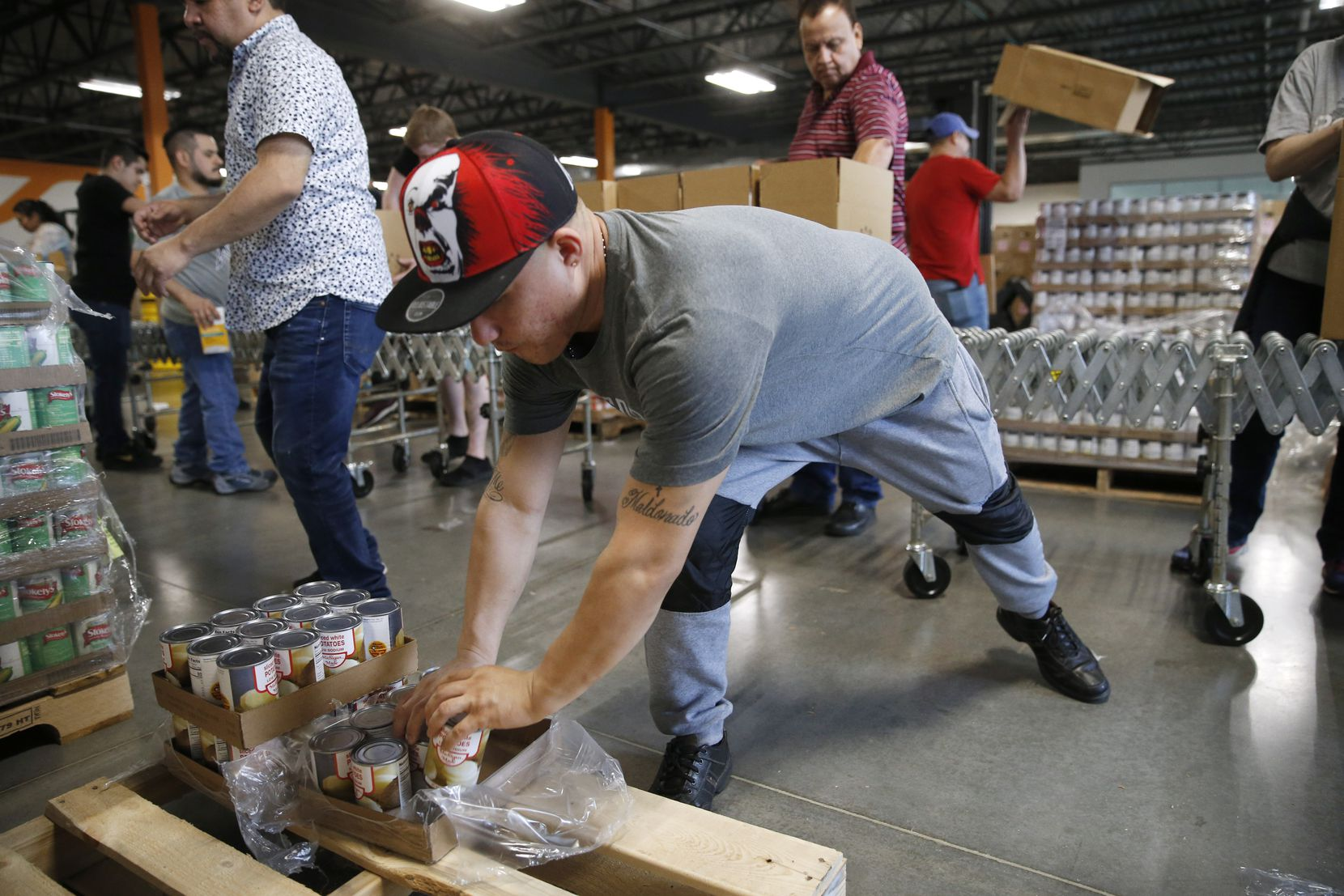 Fredy Maldonado of Dallas works on putting together boxes for distribution at North Texas Food Bank in Plano. The North Texas Food Bank is replacing volunteers with employees in the hospitality industry who have been affected by the restaurant closures due to the coronavirus.