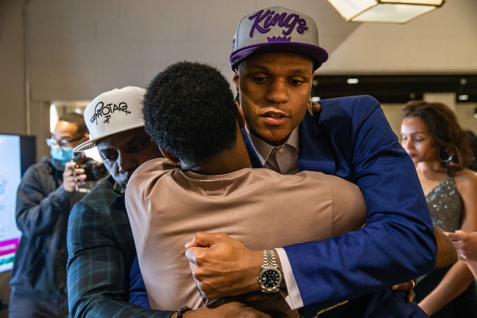 Jahmi'us Ramsey (center) receives an embrace from his father Avery (left) and brother Corinthian as they react to his selection as the 43rd pick by the Sacramento Kings during the virtual NBA Draft 2020 at The Slate coworking space in Dallas on Wednesday, Nov. 18, 2020.