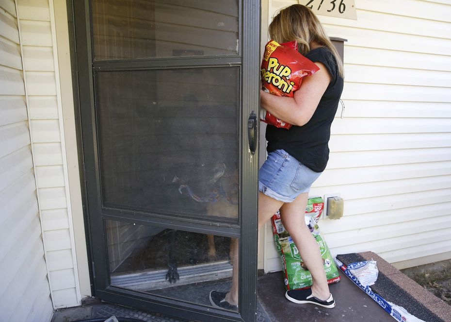 Jeanne Marie Boyne, a volunteer for the Seniors' Pet Assistance Network brings dog treats and food to a client's home in  July, 2019.