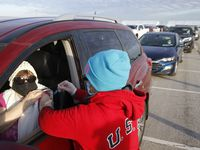 Donna Bergman of Flower Mound receives a COVID-19 vaccintation from Penny Mayo at a drive-through vaccination clinic at Texas Motor Speedway in Fort Worth.