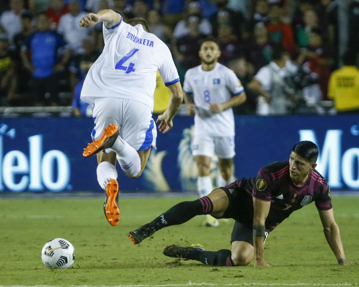 Mexico forward Alan Pulido (9) slides into El Salvador defender Eriq Zavaleta (4) during the second half of a CONCACAF Gold Cup Group A soccer match at the Cotton Bowl on Sunday, July 18, 2021, in Dallas. (Elias Valverde II/The Dallas Morning News)