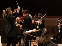 Principal guest conductor Gemma New, left, and violin soloist Augustin Hadelich perform during a Dallas Symphony Orchestra concert at the Meyerson Symphony Center.