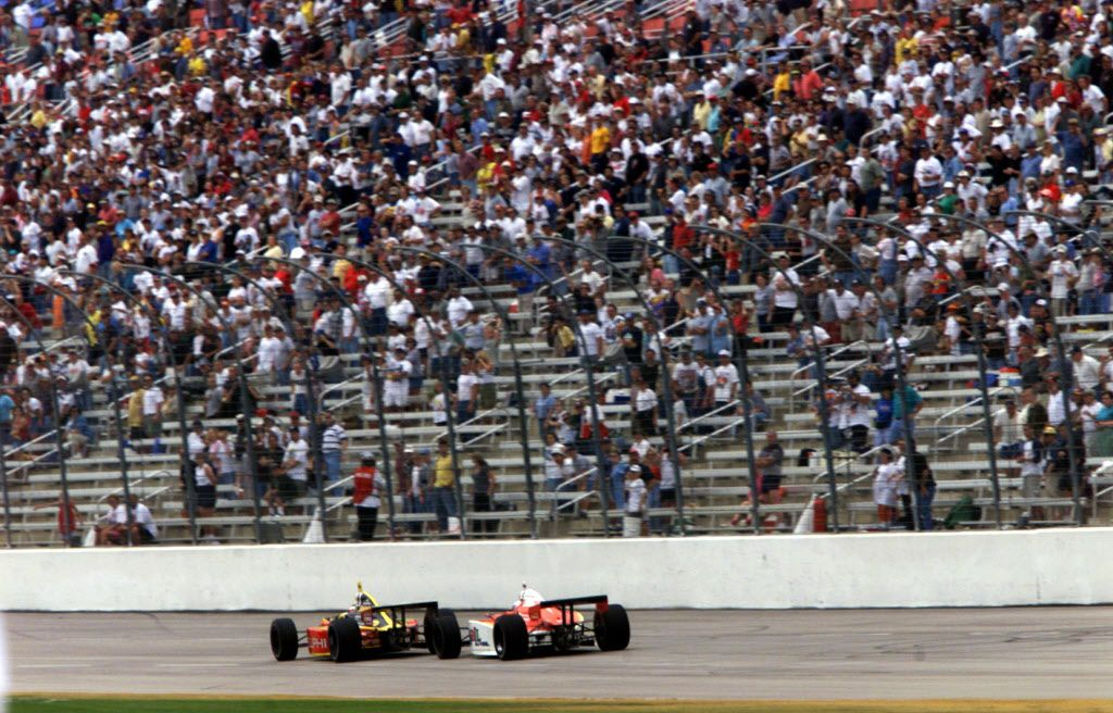 Scott Sharp keeps his lead over Robby McGehee in the front straight to take the checkered flag at the Casino Magic 500 at Texas Motor Speedway Sunday.  Scott Sharp won in the closest finish in Indy Racing Car League history.