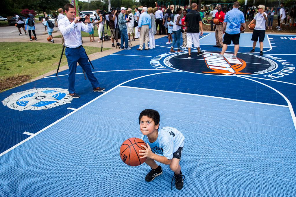 Seven-year-old Dante Harris takes a shot as the ribbons are cut on two Dream Courts at Kiest Park in Dallas.
