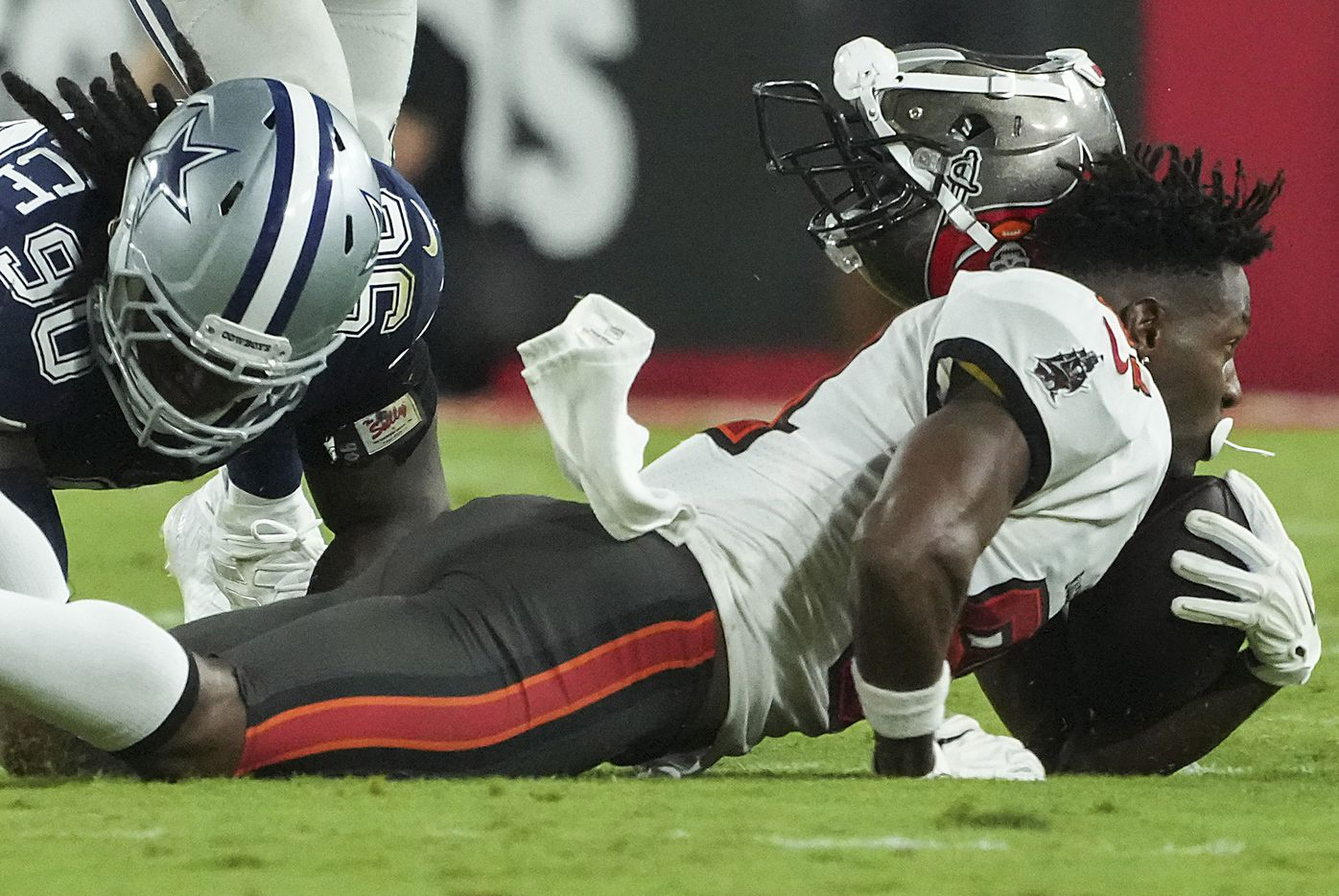 Tampa Bay Buccaneers wide receiver Antonio Brown (81) loses his helmet as he is brought down by Dallas Cowboys defensive end DeMarcus Lawrence (90) during the second half of an NFL football game at Raymond James Stadium on Thursday, Sept. 9, 2021, in Tampa, Fla. The  Buccaneers won the game 31-29. (Smiley N. Pool/The Dallas Morning News)
