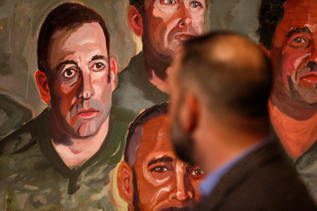 First Sgt. Robert Ferrara looks over at his portrait during a media preview of the Portraits of Courage exhibit at the George W. Bush Presidential Center in Dallas on Tuesday, Feb. 28, 2017. (Rose Baca/The Dallas Morning News)