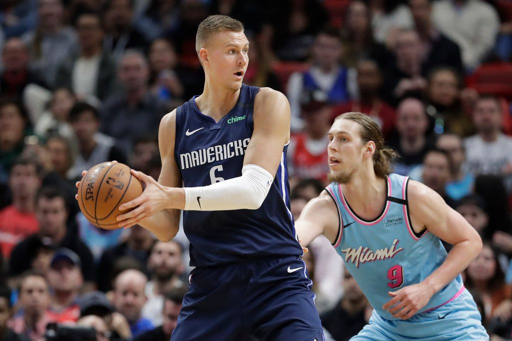Dallas Mavericks center Kristaps Porzingis (6) looks for an open teammate past Miami Heat forward Kelly Olynyk (9) during the second half of an NBA basketball game, Friday, Feb. 28, 2020, in Miami.