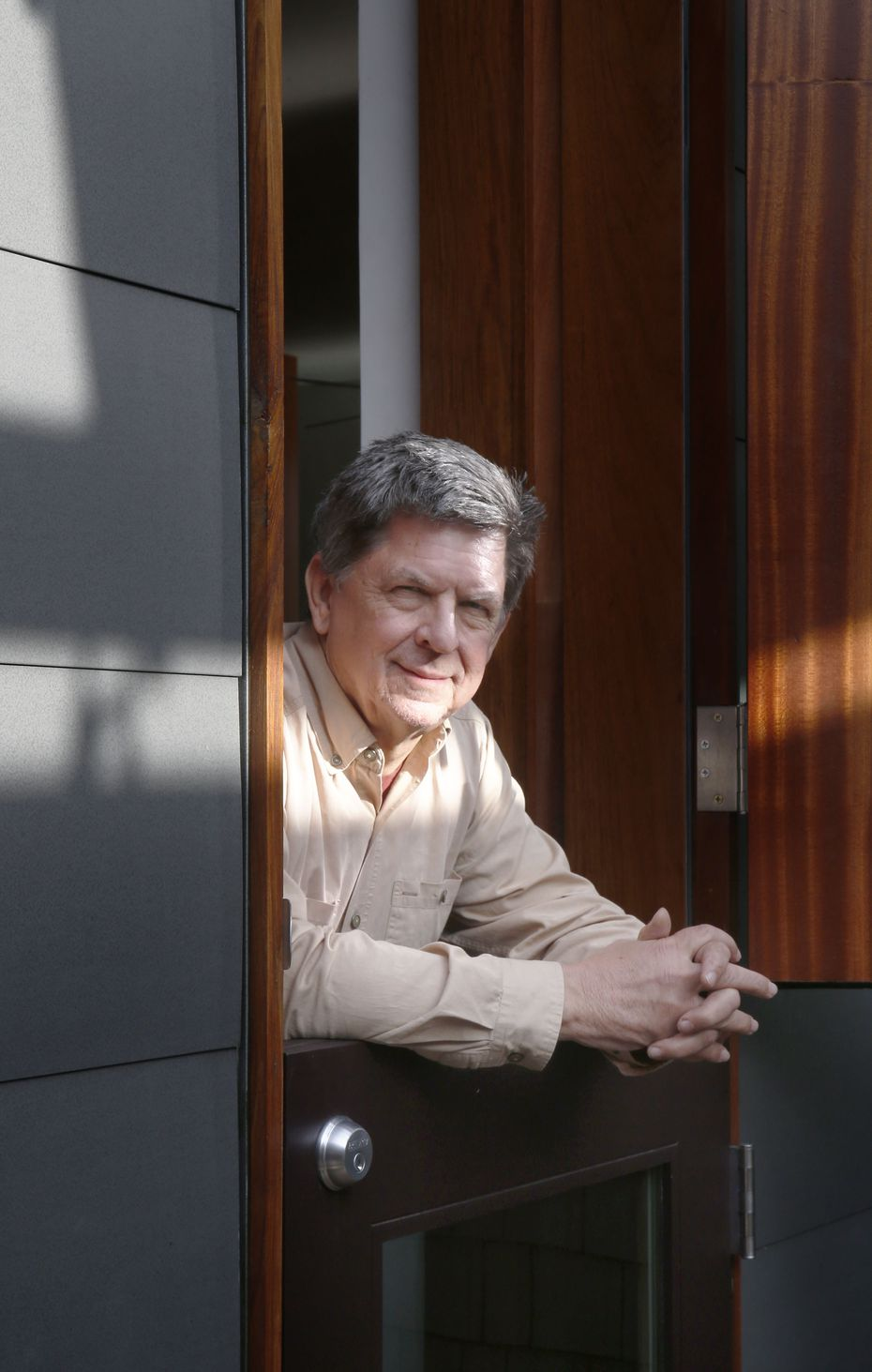 "Architect Dan Shipley poses in one of the Dutch doors whose top and bottom panels swing separately. To keep bugs out but allow in air and sound, a hidden ""pocket"" screendoor slides out of the wall."