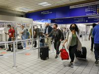 Travelers walk past a TSA checkpoint in Terminal C at DFW International Airport on Oct. 20, 2021.