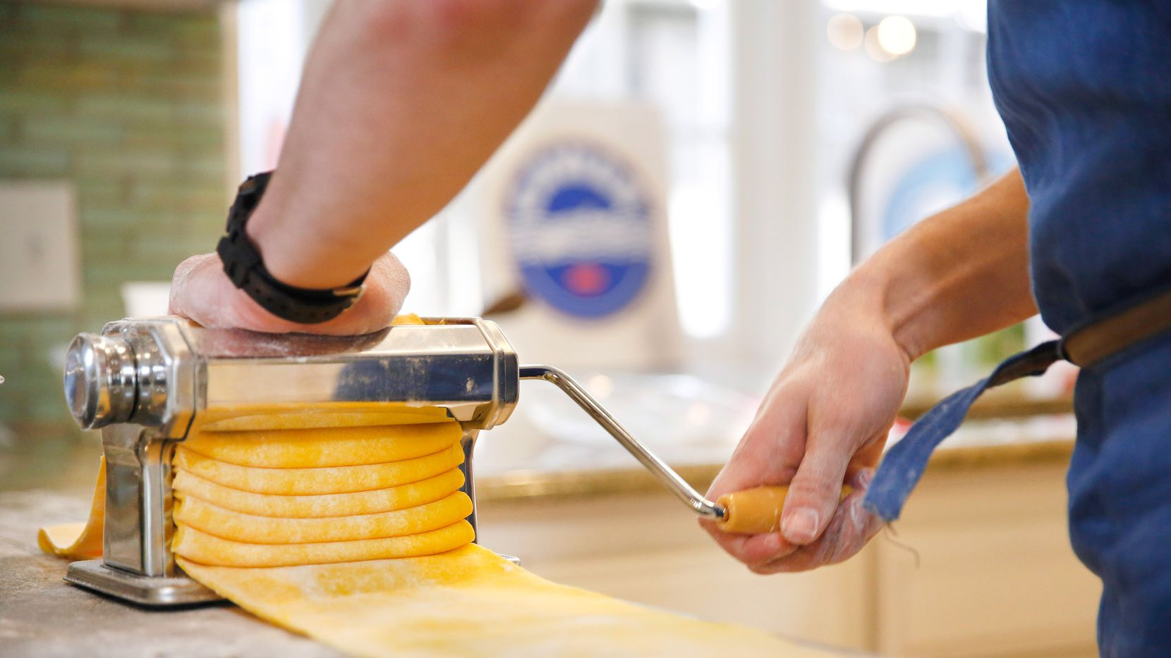 Chef Julian Barsotti uses a pasta machine to roll out lasagna sheets before par-boiling them. They will form the crust of the timpano, an elaborate, multi-layered Italian dish.
