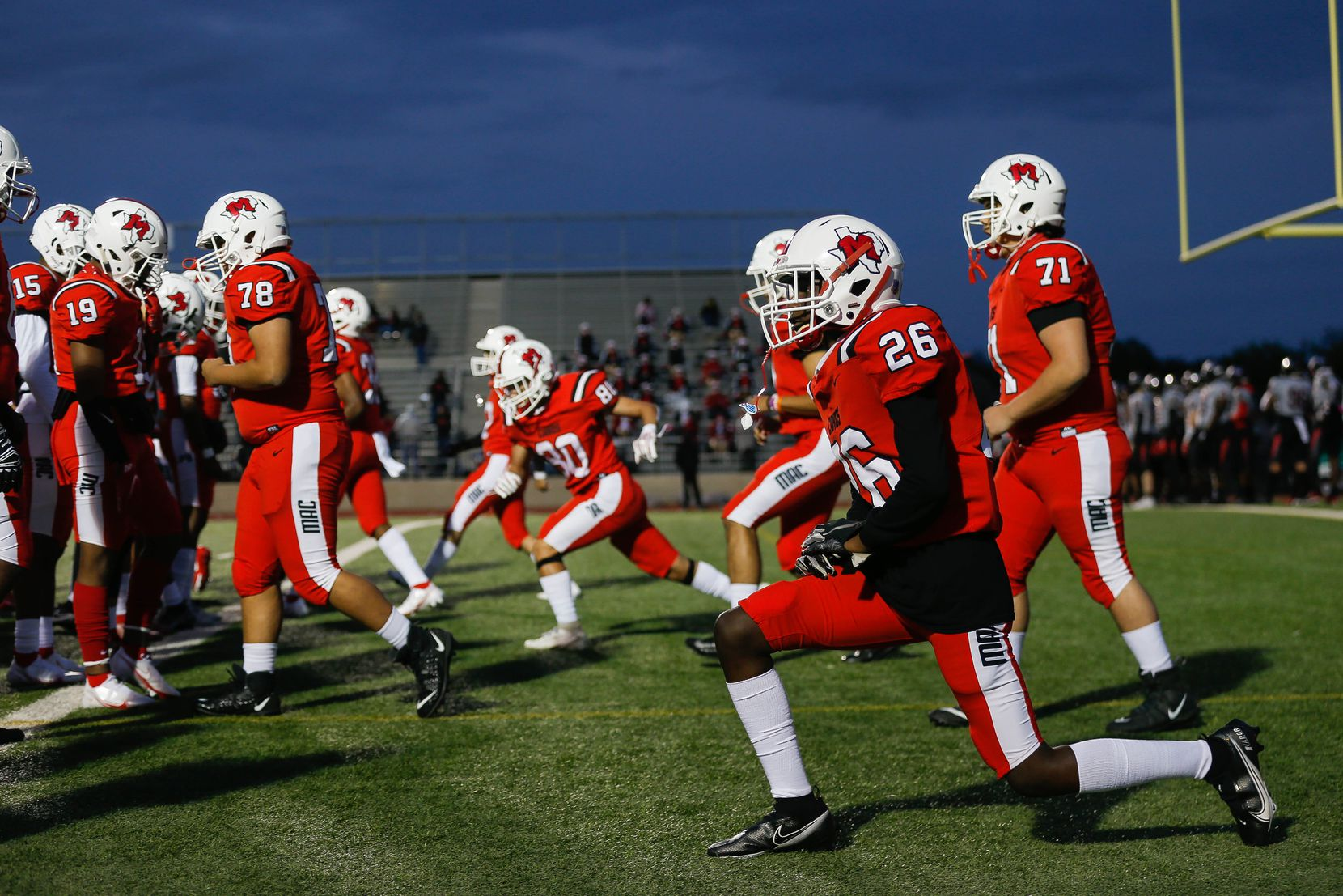 Irving MacArthur High School players stretch before a football game against Lake Highlands at Joy & Ralph Ellis Stadium in Irving on Friday, Oct. 23, 2020. (Juan Figueroa/ The Dallas Morning News)