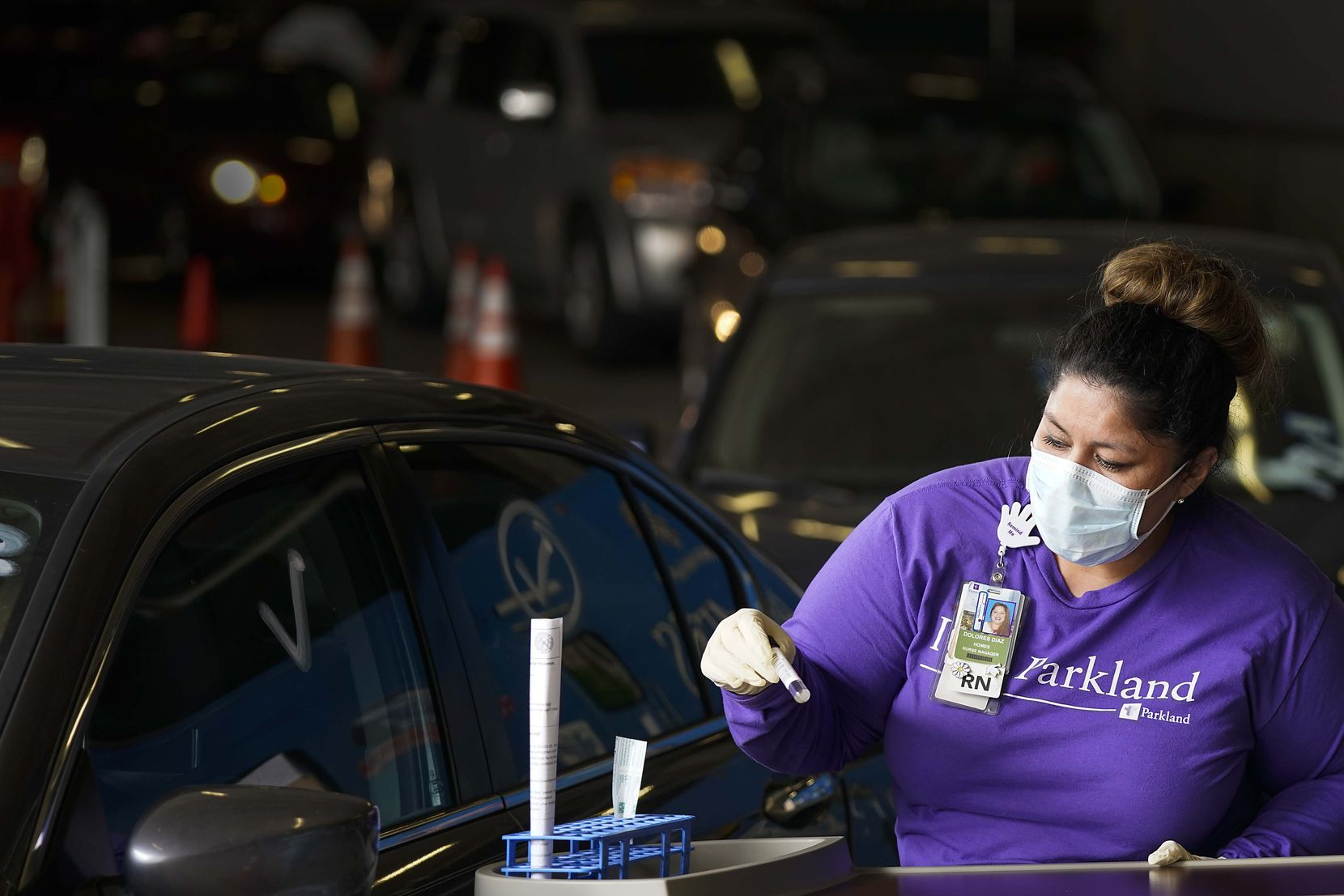 Parkland Homeless Outreach Medical Services (HOMES) program nurse manager Dolores Diaz prepares testing materials at a COVID-19 drive-through testing site at American Airlines Center on Monday, April 20, 2020, in Dallas. (Smiley N. Pool/The Dallas Morning News)