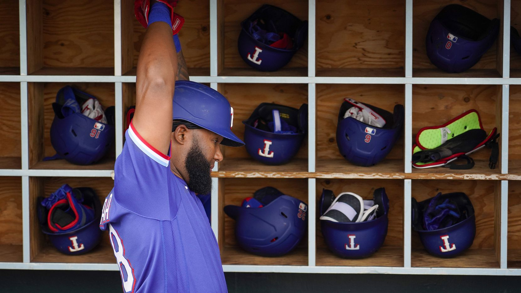 Texas Rangers outfielder Danny Santana stretches in the dugout before a spring training game against the Los Angeles Angels at Tempe Diablo Stadium on Friday, Feb. 28, 2020, in Tempe, Ariz.