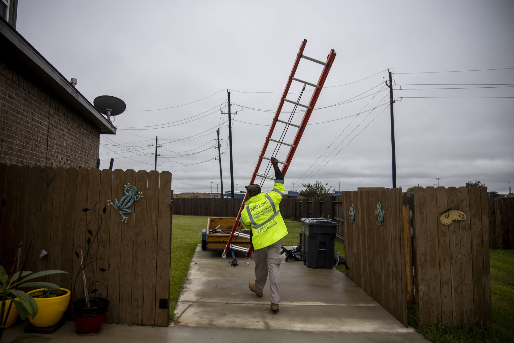 O'Neil Young, broadband installation technician for MB Link, carries a ladder as he works on installing internet for a customer. The city's fiber to the home internet service costs $75 a month for speeds of up to 1 gigabit per second.