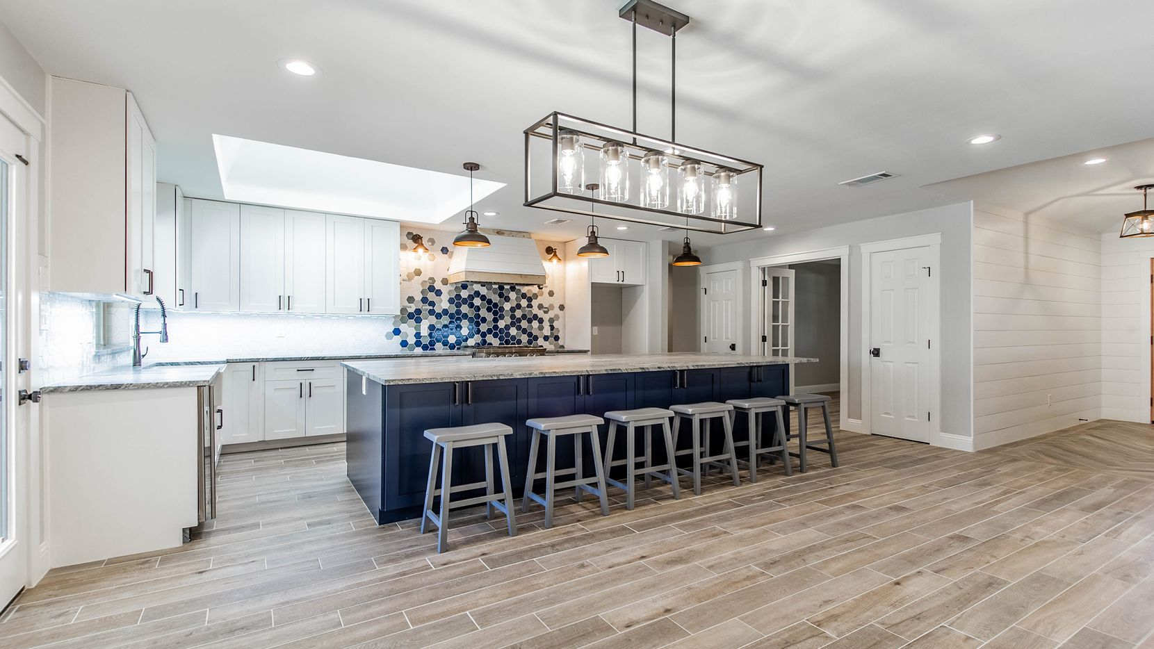 Texas Triad Homes updated this Richardson kitchen with a large navy island featuring a pullout microwave drawer and a secondary oven.