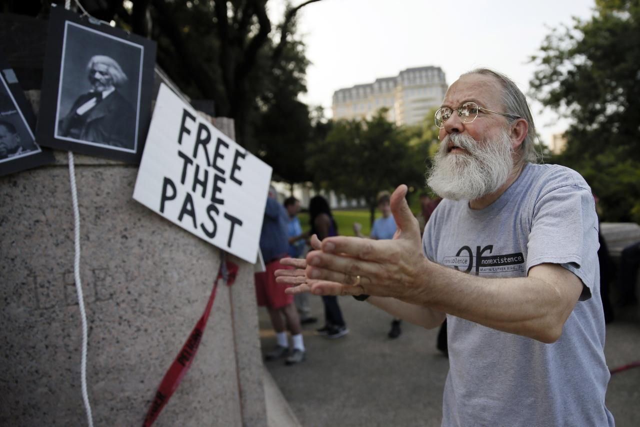 John Fullinwider led protestors as they gathered around the base of a General Robert E. Lee statue at Lee Park recently. Fullinwider says Dallas needs a conversation about what to do with the Confederate symbols around the city.