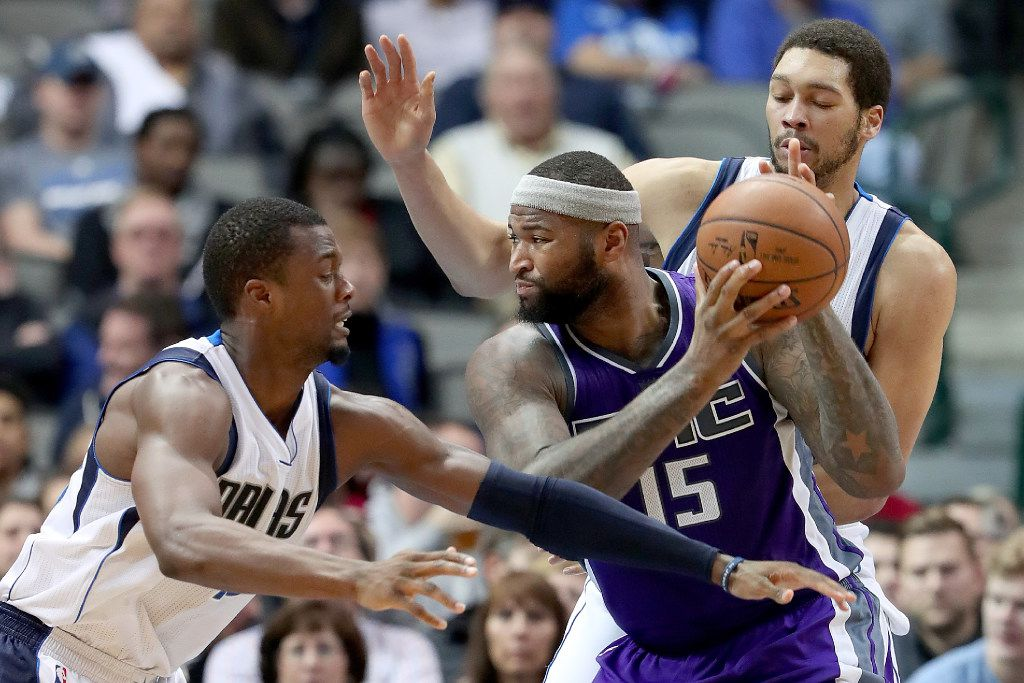 DeMarcus Cousins #15 of the Sacramento Kings drives to the basket against Harrison Barnes #40 of the Dallas Mavericks and A.J. Hammons #20 of the Dallas Mavericks in the second half at American Airlines Center on December 7, 2016 in Dallas, Texas. NOTE TO USER: User expressly acknowledges and agrees that, by downloading and or using this photograph, User is consenting to the terms and conditions of the Getty Images License Agreement.  (Photo by Tom Pennington/Getty Images)