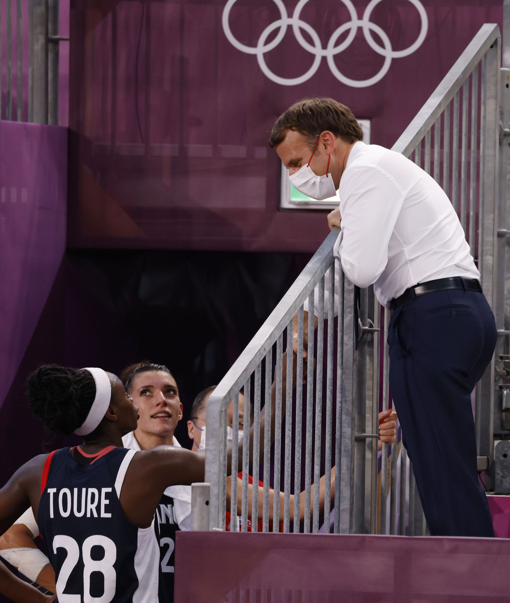 French President Emmanuel Macron talks to players from France after they lost to USA 17-10 in a 3x3 women's basketball game during the postponed 2020 Tokyo Olympics at Aomi Urban Sports Park on Saturday, July 24, 2021, in Tokyo, Japan. (Vernon Bryant/The Dallas Morning News)