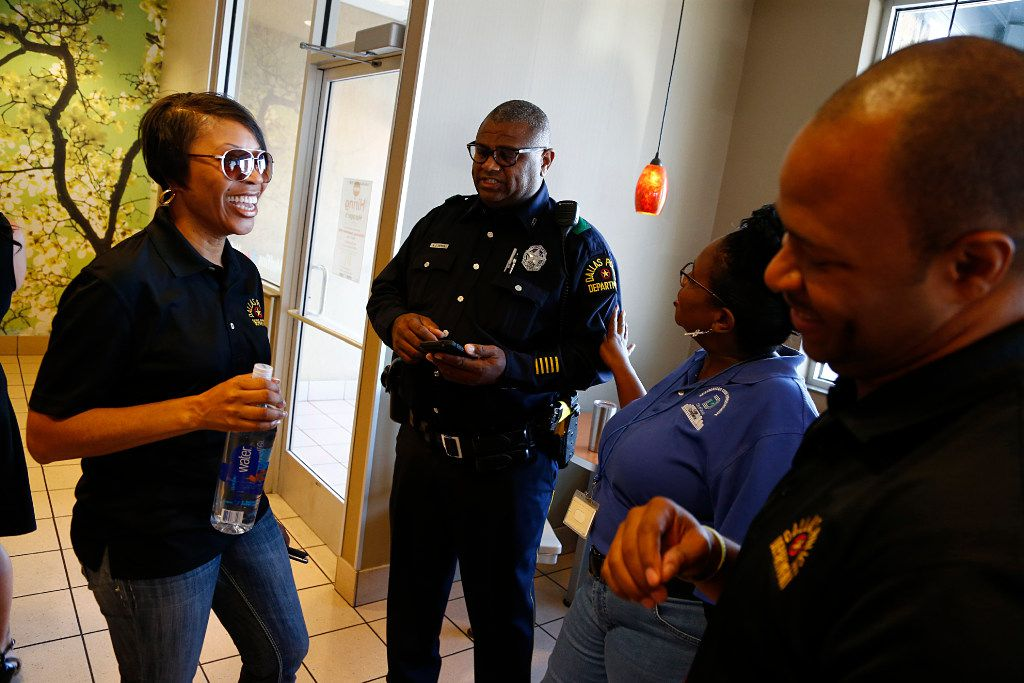 Dallas police Chief Renee Hall (left) laughs with Officer Mitchell Gatson; Michelle Lowe, neighborhood code representative; and Mandrell Drakes, community outreach representative, at a Dallas police community outreach event on Sept. 9 at a McDonald's in the Northeast Division patrol area.