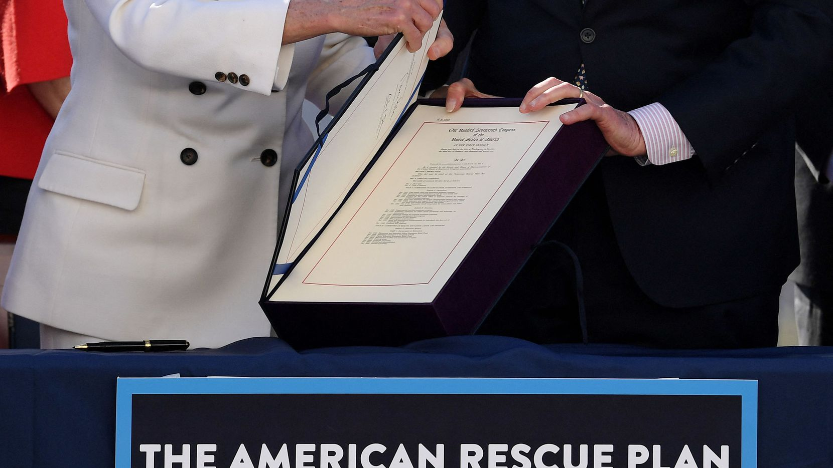 In this March 10, 2021, photo House Speaker Nancy Pelosi and Senate Majority Leader Chuck Schumer hold the signed American Rescue Plan Act after the House approved the $1.9 trillion Covid-19 relief plan.