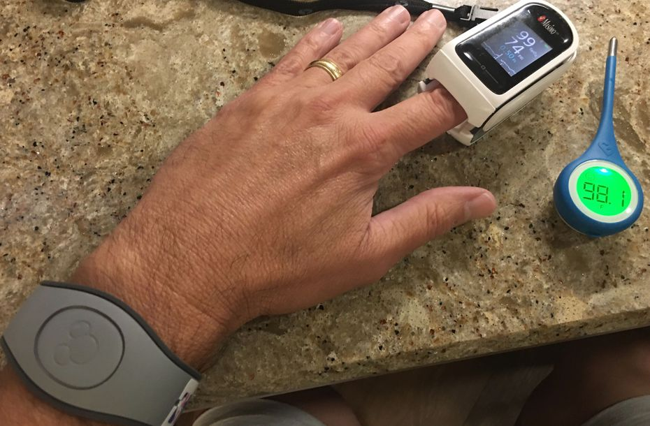 Dallas Morning News reporter Brad Townsend shows the thermometer, pulse oximeter and bracelet he uses while reporting on the Mavericks from inside the NBA bubble, at the ESPN Wide World Of Sports Complex in Lake Buena Vista, Florida.