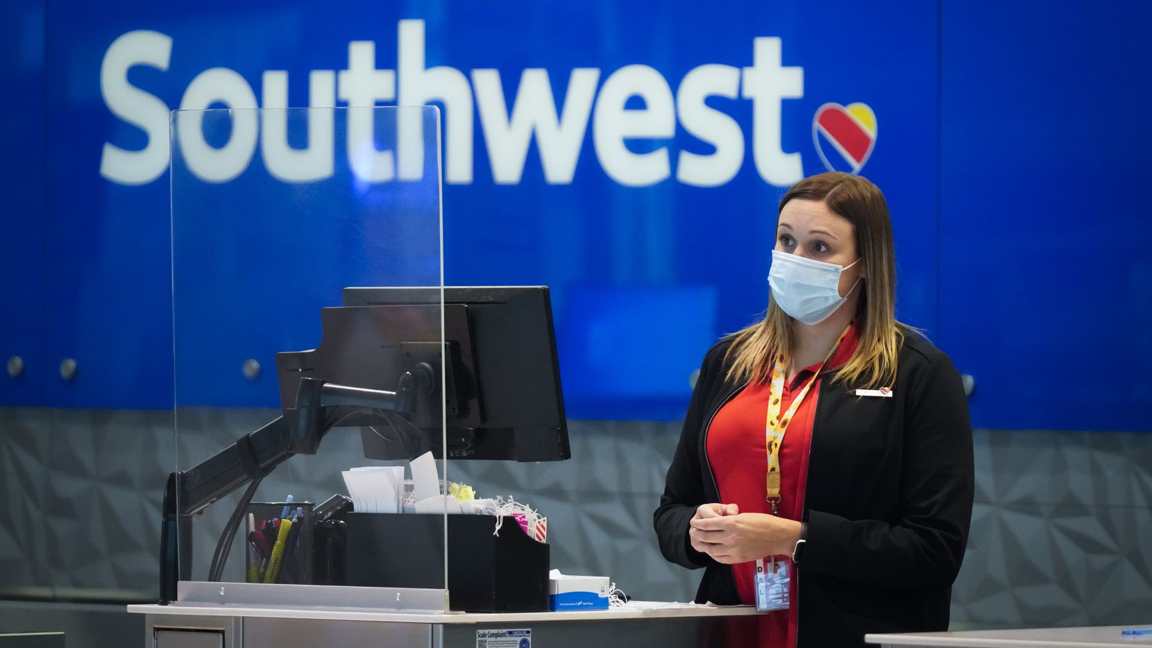 A Southwest Airlines agent works at a check-in counter at Love Field in Dallas.
