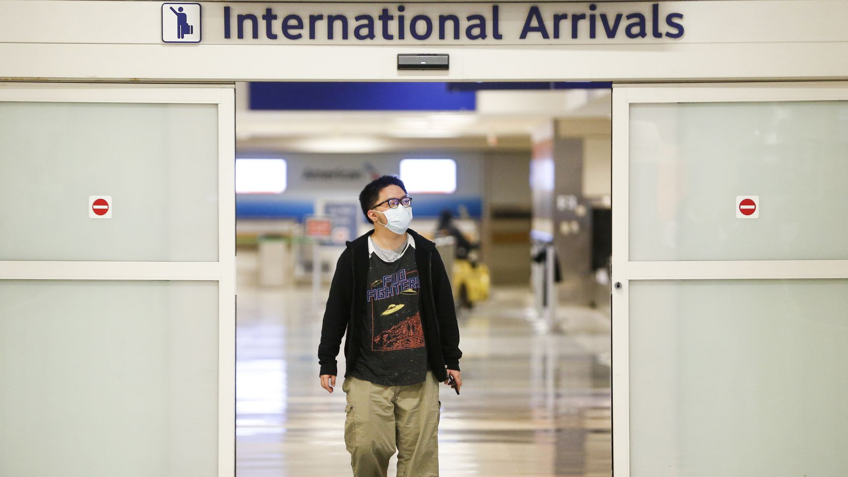 Wearing a protective mask, Frank Ye, of Shenzhen, China, arrives in the international arrivals area of DFW International Airport after a flight from Hong Kong on Tuesday, Jan. 28, 2020.