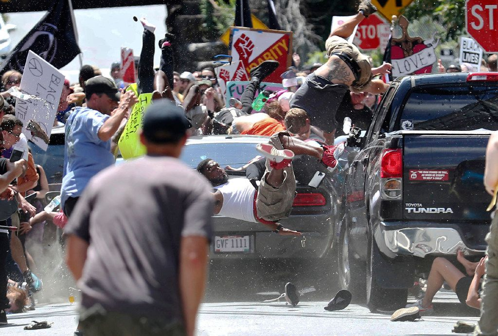 People fly into the air as a vehicle drives into a group of protesters demonstrating against a white supremacist rally in Charlottesville, Va. The group was holding the rally to protest plans by to remove a statue of Confederate Gen. Robert E. Lee. Several hundred protesters were marching in a long line when the car drove into a group of them.