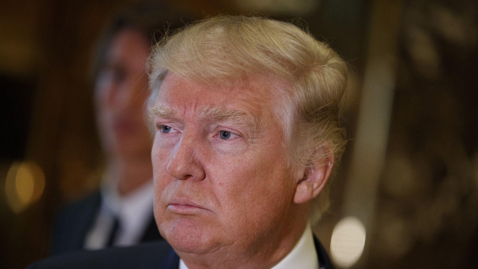 Donald Trump escucha preguntas de los reporteros en su torre en Nueva York. AP