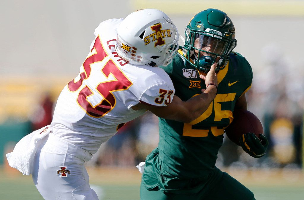 Baylor Bears running back Trestan Ebner (25) attempts to shake Iowa State Cyclones defensive back Braxton Lewis (33) during the first half of play at McLane Stadium in Waco, Texas on Saturday, September 28, 2019.
