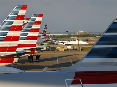 American Airlines jets are parked at Terminal C as a Skywest jet taxis to the gate at Dallas-Fort Worth International Airport, Sunday, April 19, 2020. Airlines have pared flight schedules due to the COVID-19 pandemic.
