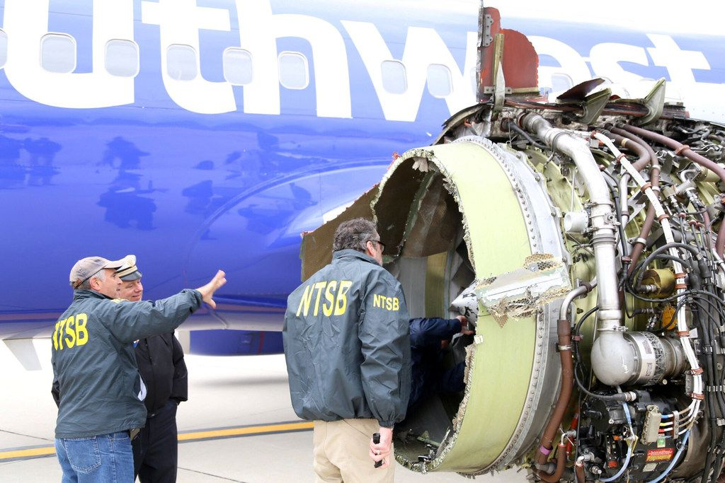 In a National Transportation Safety Board photo, investigators in Philadelphia examine the damaged engine that caused the death of a passenger on a Southwest Airlines plane on April 17, 2018. The engine on the plane failed shortly after takeoff from La Guardia Airport in New York, killing a woman sitting in a window seat near the blast. (National Transportation Safety Board via The New York Times)