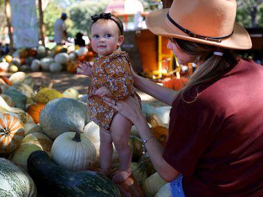 Sarah Clark holds 10-month-old Raegan in the Pumpkin Village at the Dallas Arboretum.