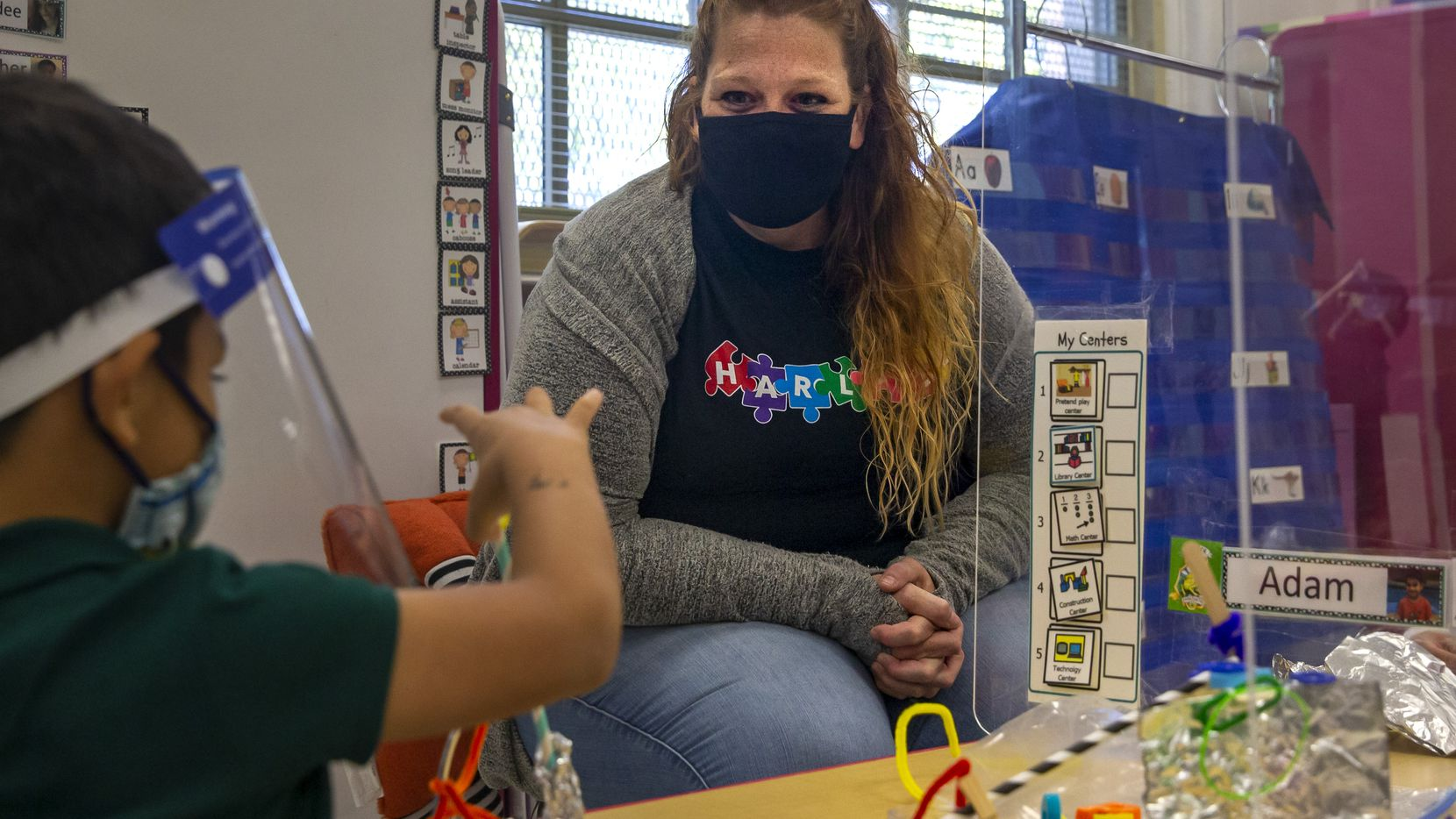 Pre-K 4 teacher Annie Pardee cheers on student Adam Renteria as he and his classmates work on an activity behind sneeze guards installed on their desks at N.W. Harllee Early Childhood Center in the Oak Cliff neighborhood of Dallas on Friday, Oct. 2, 2020. Dallas ISD's Pre-K numbers are down by the thousands to start the school year. (Lynda M. González/The Dallas Morning News)