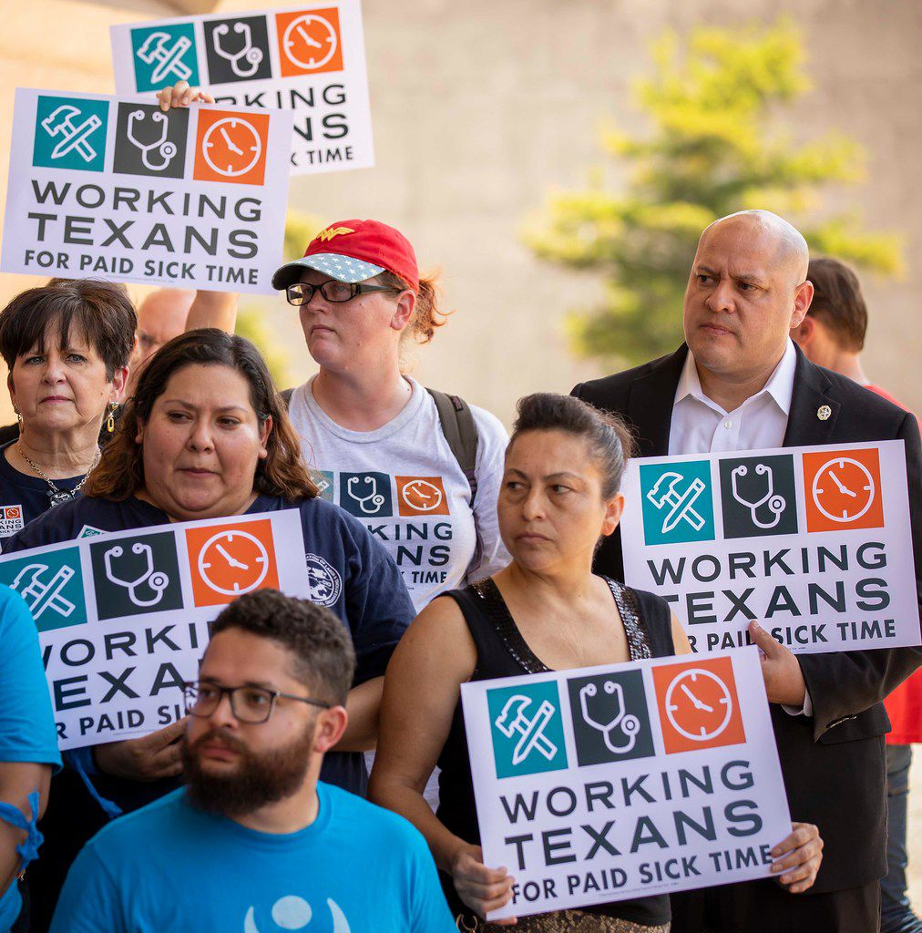 City Council member Adam Medrano (right) held a sign during a June 2018 news conference before a coalition of labor and faith groups and political activists delivered petitions to City Hall calling for a city ordinance mandating paid sick time to be placed on last November's ballot. The petition drive failed, but Medrano and his council colleagues passed an ordinance in April.