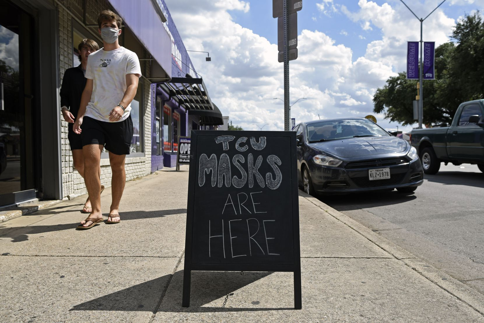 Texas Christian University students walk by signage for masks outside of Flash The University Store on University Drive outside of the campus of TCU in Fort Worth, Aug. 27, 2020. TCU went from 111 COVID-19 cases on Monday to 360 cases on today. Ben Torres/Special Contributor