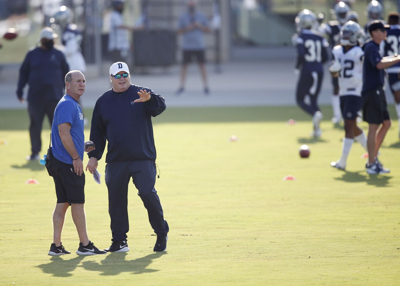 Dallas Cowboys head coach Mike McCarthy talks with Dallas Cowboys equipment coordinator Bucky Buchanan during practice on the first day of training camp at Dallas Cowboys headquarters at The Star in Frisco, Texas on Friday, August 14, 2020. (Vernon Bryant/The Dallas Morning News)