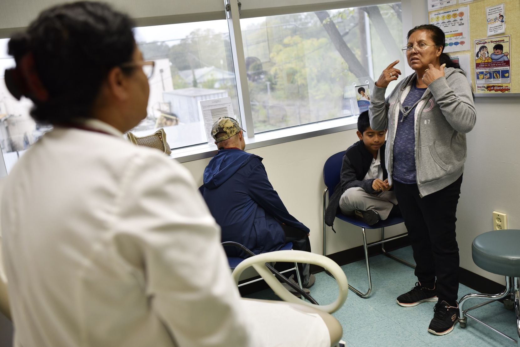 Nurse Practitioner Jhudy Mohan (left) listened as Maria Martinez described her son's symptoms during a visit at Los Barrios Unidos Community Clinic in Dallas on Tuesday.