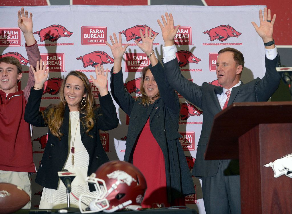 Newly hired University of Arkansas NCAA college football head coach Chad Morris, right, is joined by family members, from left, son Chandler, daughter Mackenzie and wife, Paula, as they lead a hog call during an introductory press conference in Fayetteville, Ark., Thursday, Dec. 7, 2017. (Andy Shupe/The Northwest Arkansas Democrat-Gazette via AP)