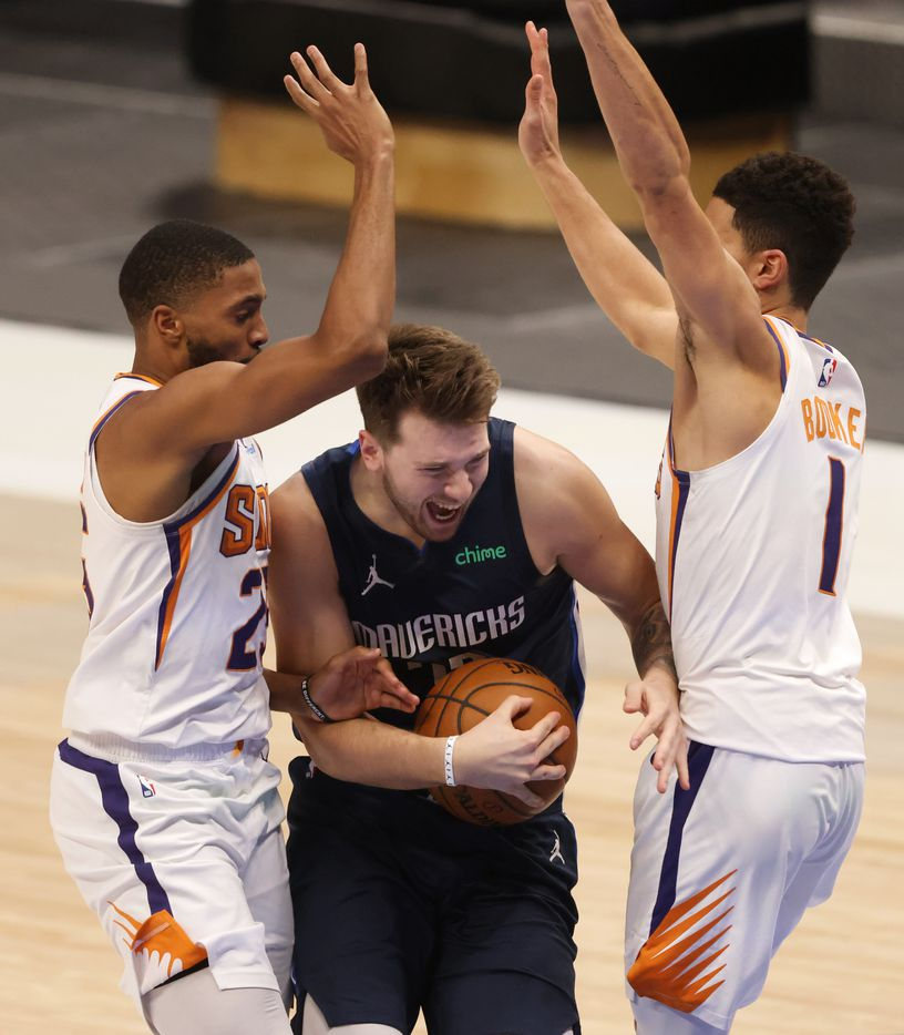 Dallas Mavericks guard Luka Doncic (77) attempts to split Phoenix Suns forward Mikal Bridges (25) and Phoenix Suns guard Devin Booker (1) on a drive to the basket during the second quarter of play at American Airlines Center on Monday, February 1, 2021in Dallas. (Vernon Bryant/The Dallas Morning News)