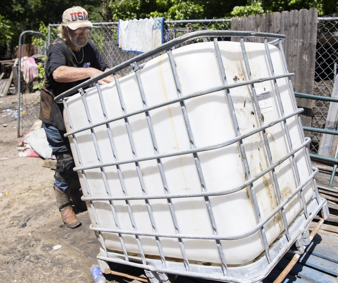 Richard Shivers flips over the water container tank he uses to transport water to the lot where he lives in Sandbranch on Wednesday, May 26, 2021.