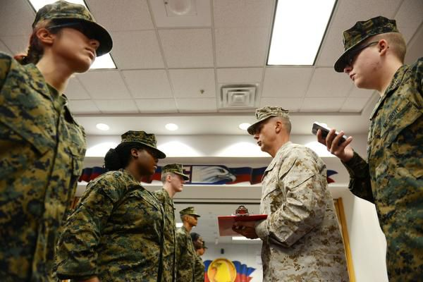 Maj. Tom Connor, lead instructor for Allen High School's Junior ROTC program, performs a uniform check on Cadet Cpl. Zaravia Griffin, while Cadet Cpl. Caroline Baca (left) looks on and Cadet Capt. Cameron Cox keeps time. In its first year, more than 320 students signed up for the U.S. Marine Corps JROTC classes that involve after-school activities.