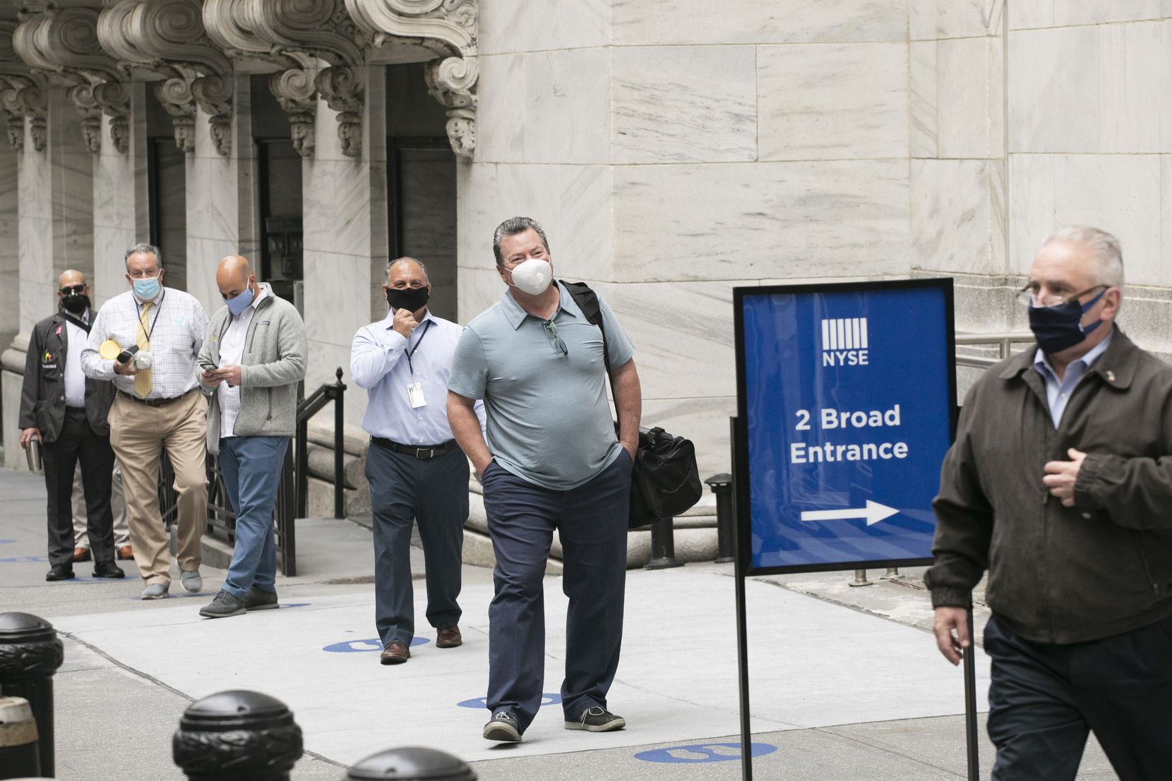 New York Stock Exchange employees wait to enter the building as the trading floor partially reopened on Tuesday.