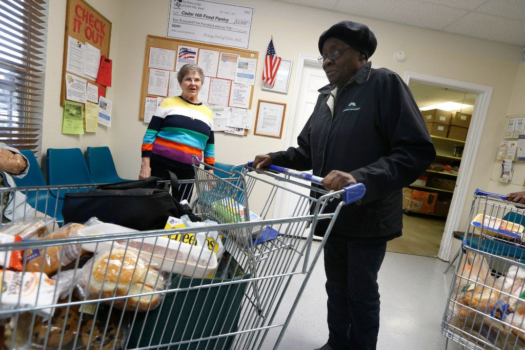 Gene Sims, executive director of Cedar Hill Shares, watches as Theresa Sanders, 78, takes her groceries out of the food bank. Dec. 31 is Sims' last day at the pantry's helm. Earlier this year, she announced plans to retire. (Nathan Hunsinger/The Dallas Morning News)