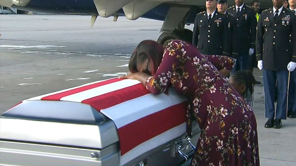 "Myeshia Johnson cries over the casket of her husband, Sgt. La David Johnson, who was killed in an ambush in Niger, upon his body's arrival in Miami. President Donald Trump told the widow that her husband ""knew what he signed up for,"" according to Rep. Frederica Wilson, who said she heard part of the conversation on speakerphone. In a Wednesday morning tweet, Trump said Wilson's description of the call was ""fabricated."""