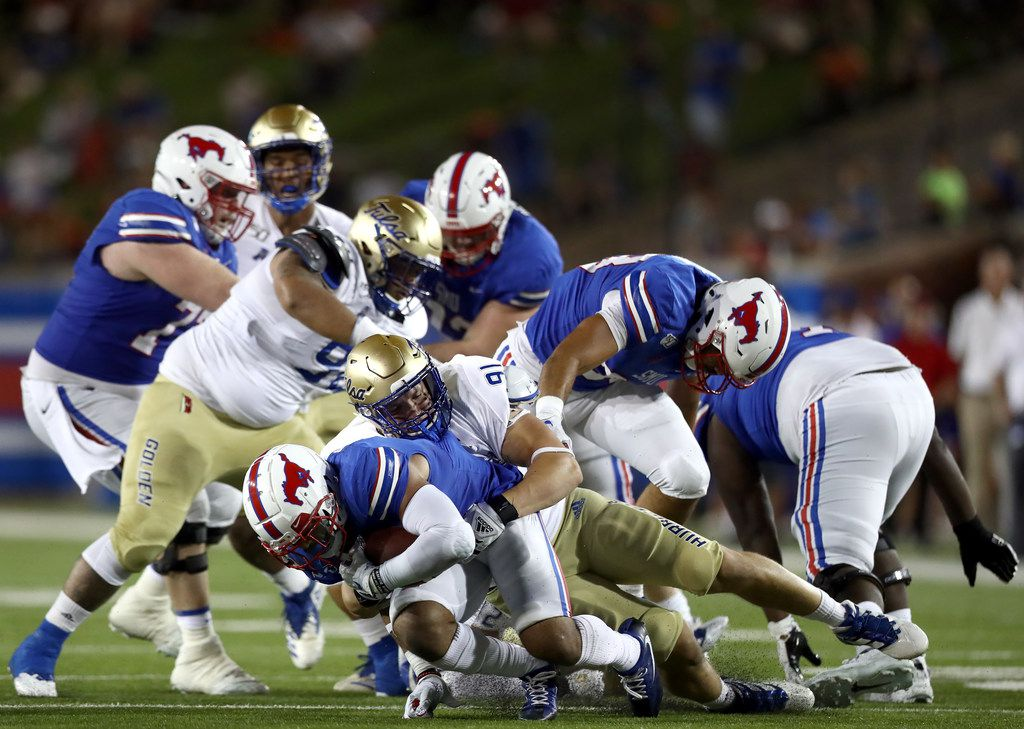 DALLAS, TEXAS - OCTOBER 05:  Xavier Jones #5 of the Southern Methodist Mustangs is tackled by Cullen Wick #91 of the Tulsa Golden Hurricane in the second quarter at Gerald J. Ford Stadium on October 05, 2019 in Dallas, Texas. (Photo by Ronald Martinez/Getty Images)