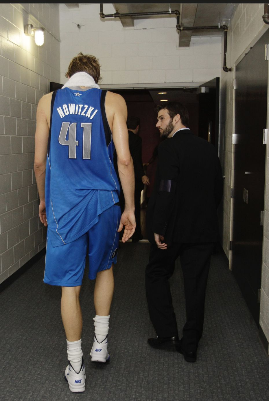 Scott Tomlin, now the Mavericks vice president of basketball communications, walks back up the AmericanAirlines Arena tunnel to the court with Dirk Nowitzki after Dallas' Game 6 victory in the 2011 NBA Finals. Tomlin was instrumental in convincing Nowitzki to return to the court to participate in the trophy ceremony.