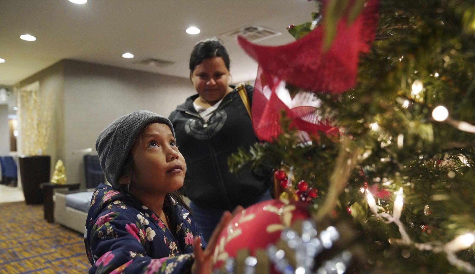 Una niña de 7 años observa un árbol de Navidad en el hotel donde ella y su madre, Isabel de 21 años, pasarán la noche tras ser procesadas en el puerto de entrada de Brownsville, Texas, el martes 17 de diciembre de 2019.